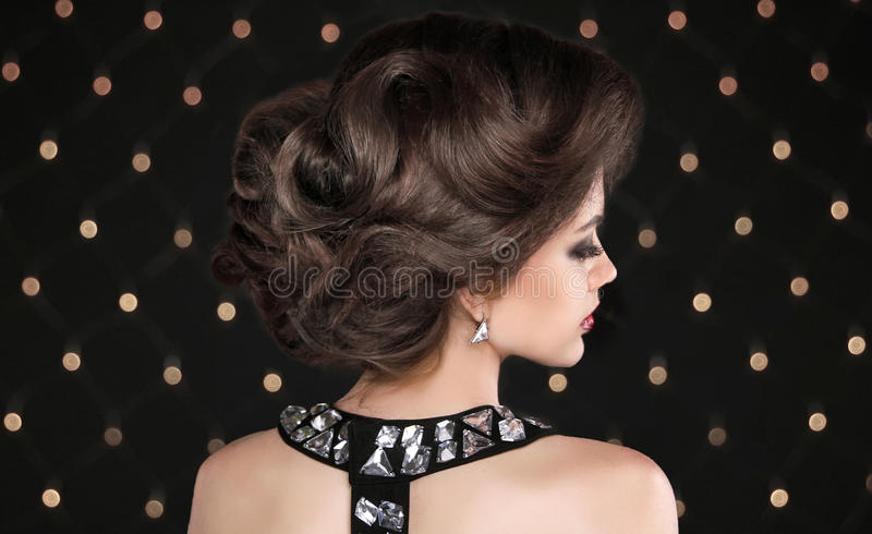 Hairstyle. Brunette woman with wavy retro hair styling. Fashion girl model on black background with lights royalty free stock photos
