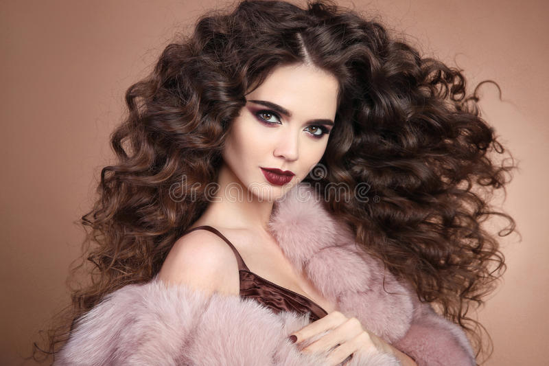 Hairstyle. Curly hair. Fashion brunette girl with long curly hair. Beauty makeup. Glamour portrait of beautiful brunette with mar royalty free stock images