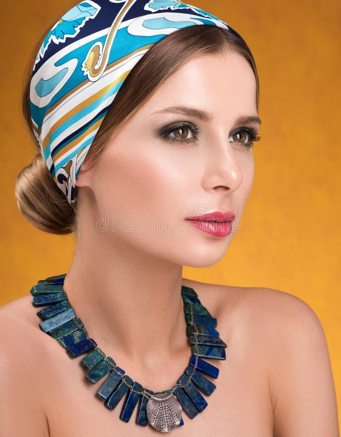 Hairstyle with headscarf. Closeup portrait of young woman with necklace stock images