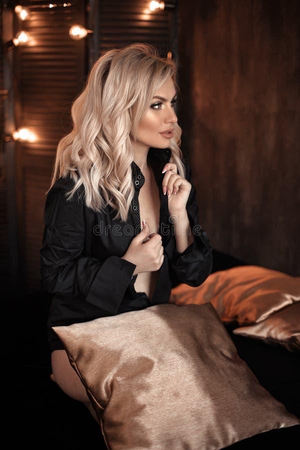 hairstyle Het mooie het portret van de blondevrouw stellen in zwart overhemd Het modieuze blonde meisjesmodel over bokeh steekt d stock foto