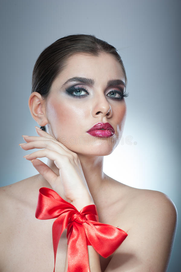 Hairstyle and Make up - beautiful female art portrait with red ribbon. Elegance. Genuine Natural brunette with ribbon - studio. Shot. Portrait of a attractive stock photo