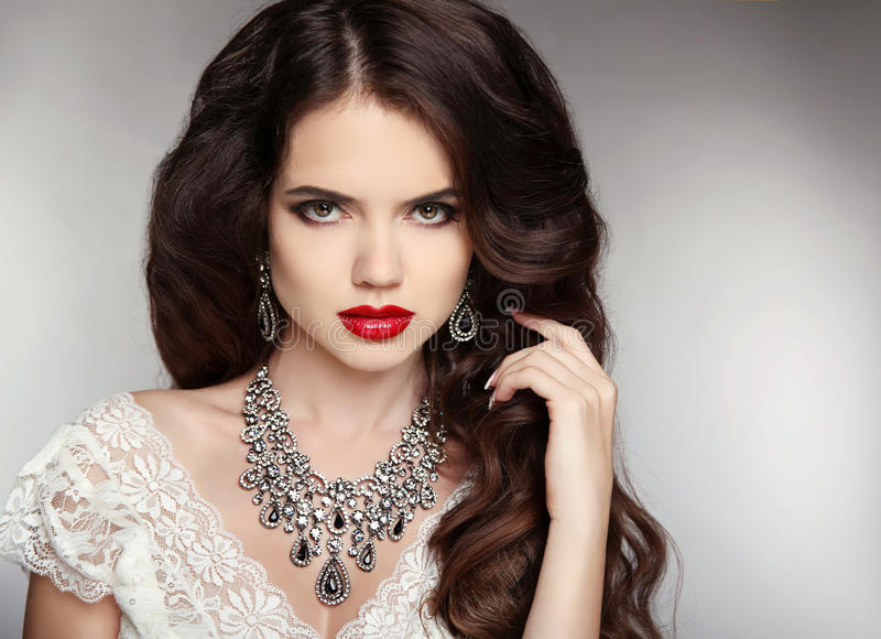 Hairstyle. Makeup. Jewelry. Beautiful woman with curly hair and royalty free stock photos