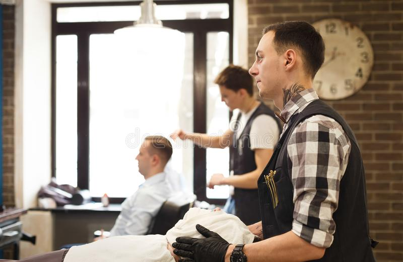 Man getting haircut by hairstylist at barbershop royalty free stock images