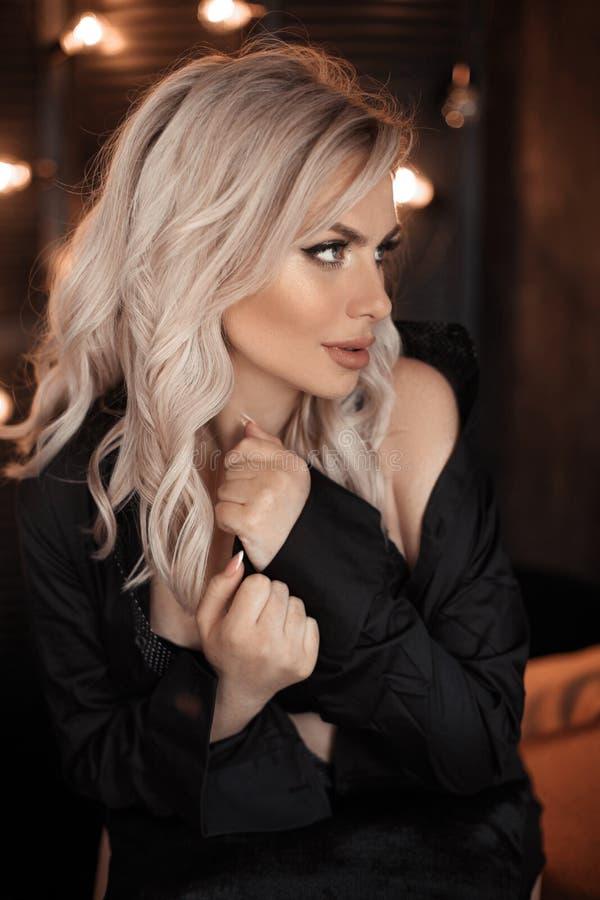 hairstyle Retrato rubio hermoso de la mujer que presenta en camisa negra Modelo rubio de moda de la muchacha sobre fondo oscuro d imagen de archivo