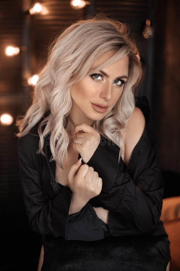 hairstyle Retrato rubio hermoso de la mujer que presenta en camisa negra Modelo rubio de moda de la muchacha sobre fondo oscuro d foto de archivo libre de regalías