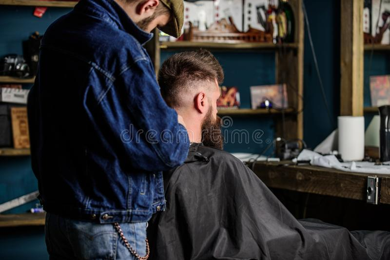 Hairstyle service concept. Barber with clipper works on hairstyle for bearded man, barbershop background. Hipster. Bearded client got hairstyle. Barber with stock image