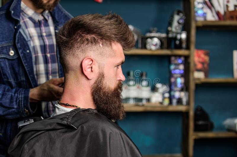 Hairstyle service concept. Hipster bearded client got hairstyle. Barber with clipper works on hairstyle for bearded man. Barbershop background. Barber with royalty free stock photos