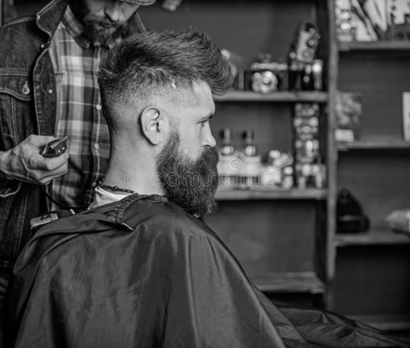 Hairstyle service concept. Hipster bearded client got hairstyle. Barber with trimmer or clipper shaved neck of client. Barber with clipper works on hairstyle royalty free stock images