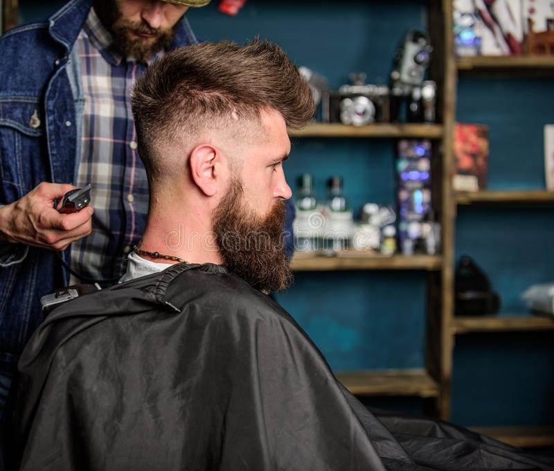 Hairstyle service concept. Hipster bearded client got hairstyle. Barber with trimmer or clipper shaved neck of client. Barber with clipper works on hairstyle stock photography