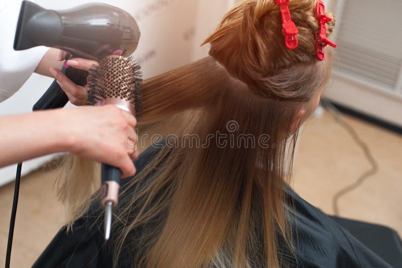Hairstyler med ett borsteuttorkninghår av en kvinna i en salong arkivfoton