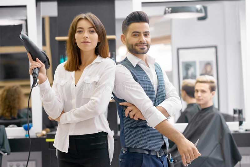 2 hairstylers представляя стоять в салоне современного spacy beaty стоковое фото