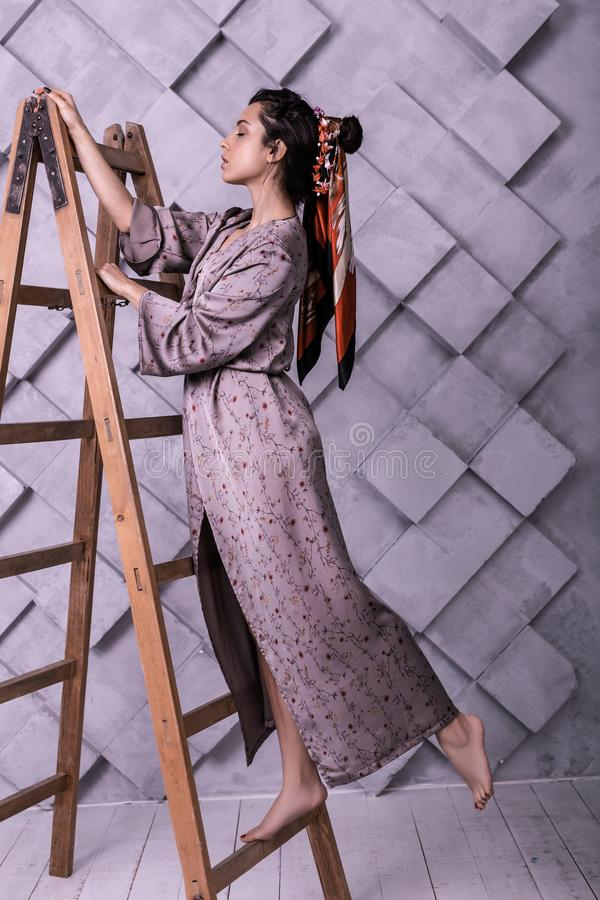 Prepossessing poser wearing dress standing on ladder during studio shooting. Hairstyles look book. Prepossessing sophisticated with finely-cut face poser wearing stock photo