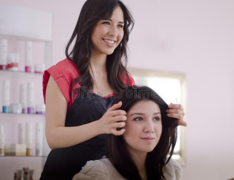 Hairstylist adding the finishing touches. Cute female hairstylist adding the finishing touches to a customer's hair stock images