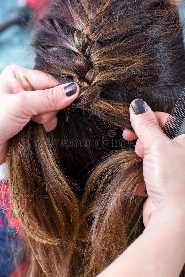 Hairstylist braiding the brown hair of a woman stock images