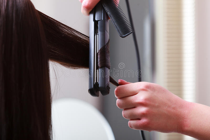 Hairstylist curling hair woman client in hairdressing beauty salon stock photo