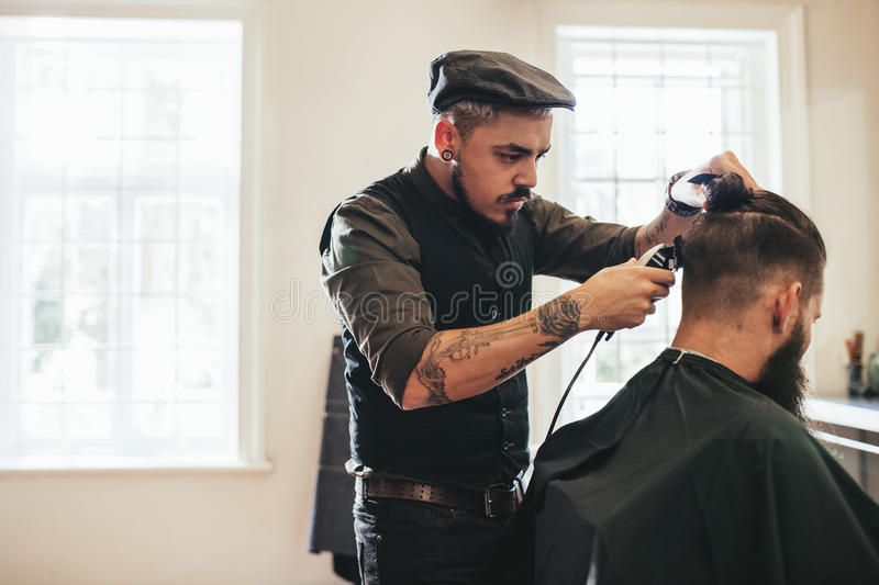 Hairstylist cutting hair of customer at barber shop stock image