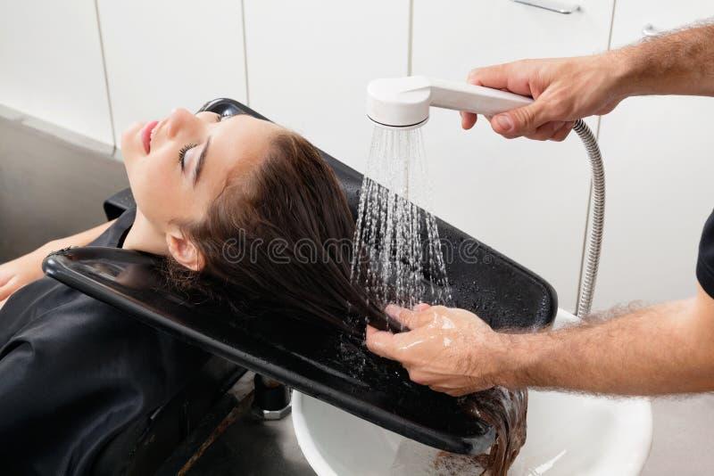 Hairstylist klienta Płuczkowy włosy Przy bawialnią zdjęcie royalty free