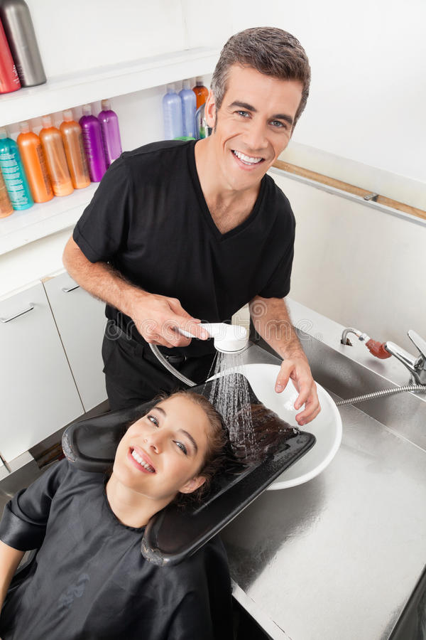 Hairstylist klienta Płuczkowy włosy W bawialni obraz stock