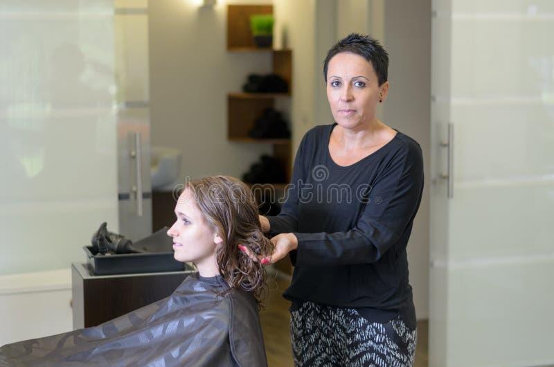 Hairstylist kobiety naprawiania włosy Żeński klient obraz stock