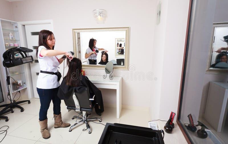 Hairstylist kobiety suszarniczy włosiany klient w fryzjerstwa piękna salonie obraz stock