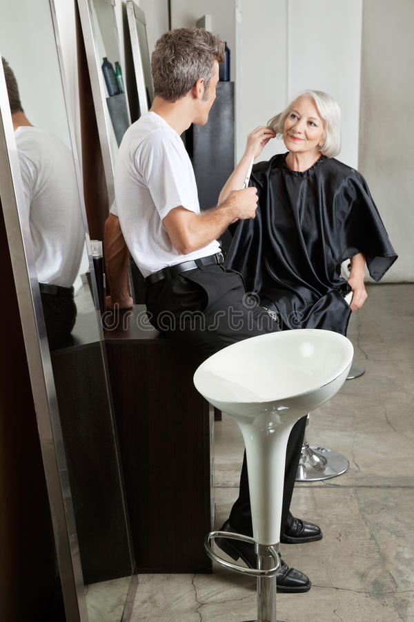 Hairstylist Listening To Female Client. Male hairstylist listening to female client at beauty salon stock images