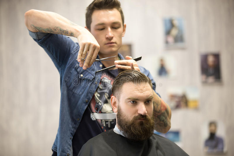 Hairstylist making haircut for male client royalty free stock photo