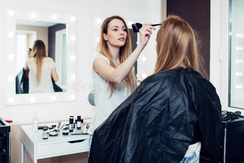 Hairstylist parting the long fair hair of young female customer sitting in cape at hairdressing salon royalty free stock image