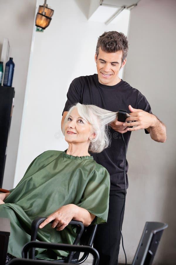 Hairstylist Prostuje Żeńskiego klienta włosy obraz royalty free