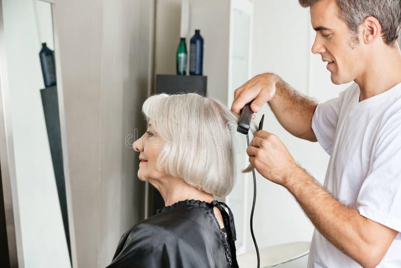 Hairstylist Prostuje klienta włosy obrazy royalty free