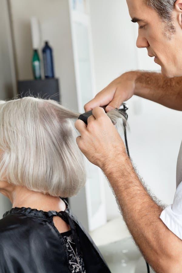 Hairstylist Prostuje klienta włosy Przy obrazy royalty free