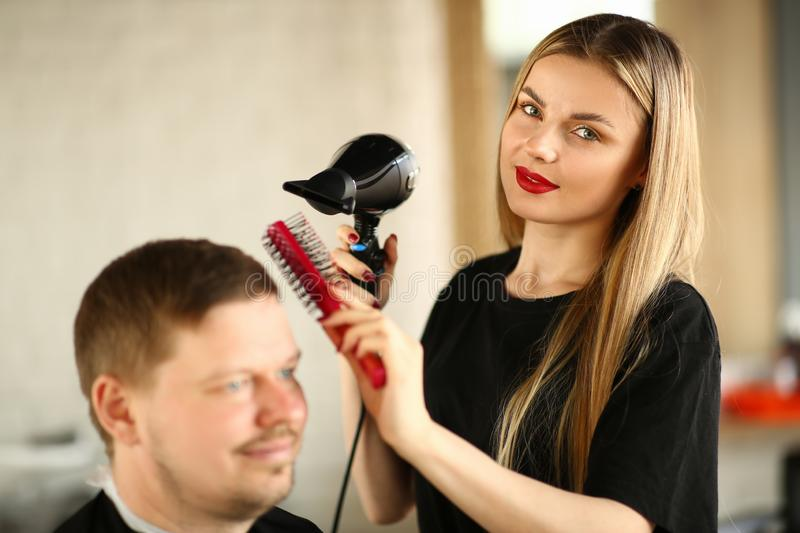 Hairstylist Styling Hairdo with Dryer and Comb. Young Hairdresser Using Hairdryer and Hairbrush Drying for Haircut Styling. Woman Stylist Drying Male Hairdo in royalty free stock photos