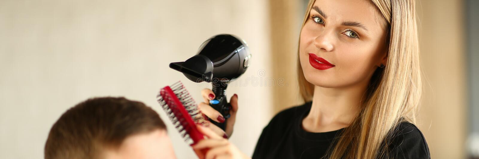 Hairstylist Styling Hairdo with Dryer and Comb. Young Hairdresser Using Hairdryer and Hairbrush Drying for Haircut Styling. Woman Stylist Drying Male Hairdo in royalty free stock images