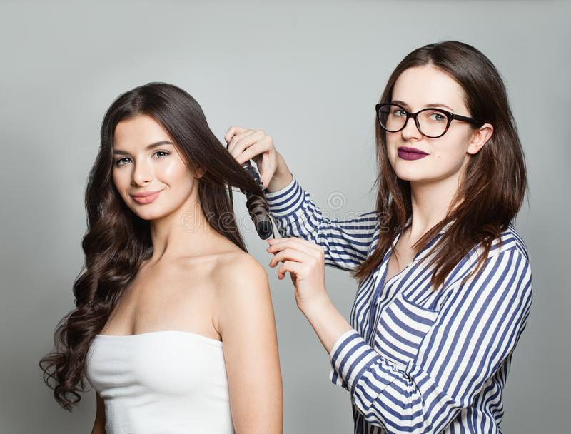Hairstylist Using Curler For Perfect Curls. Hairdresser or Hairstylist Using Curler For Perfect Curls. Hairstyle And Hairdressing. Woman Making Curls on Long stock images