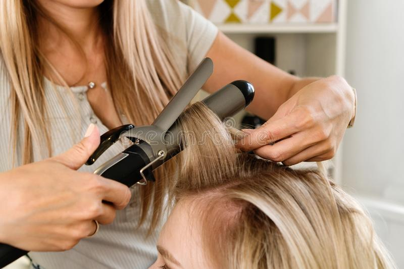Creating hairstyle. Hairstylist using curling iron of female client in hairdressing salon, closeup view. Hairdressing services. Creating hairstyle. Hair styling stock photography