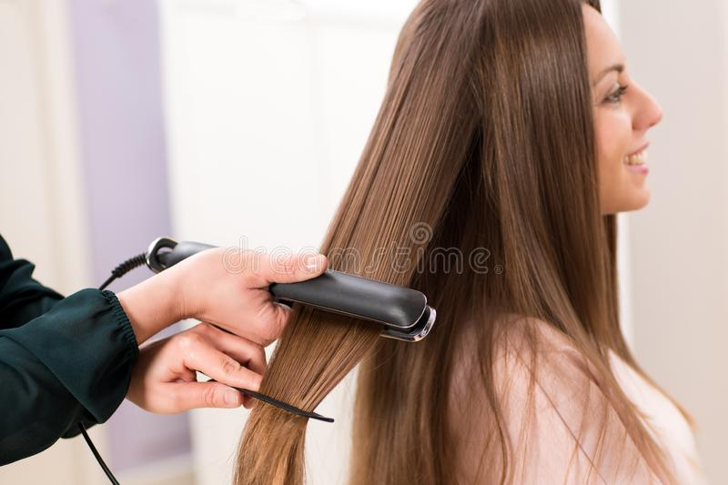Hairstylist using a flat iron on long brown hair stock photo