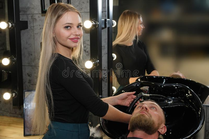 Hairstylist washing client`s hair in barber shop royalty free stock photography