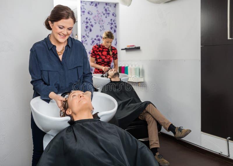 Hairstylists Myje klientów Włosianych Przy salonem zdjęcia royalty free