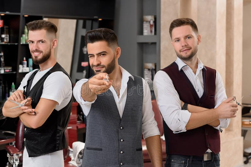 Hairstylists posing, bearded barber pointing with scissors at camera and winking. royalty free stock photos