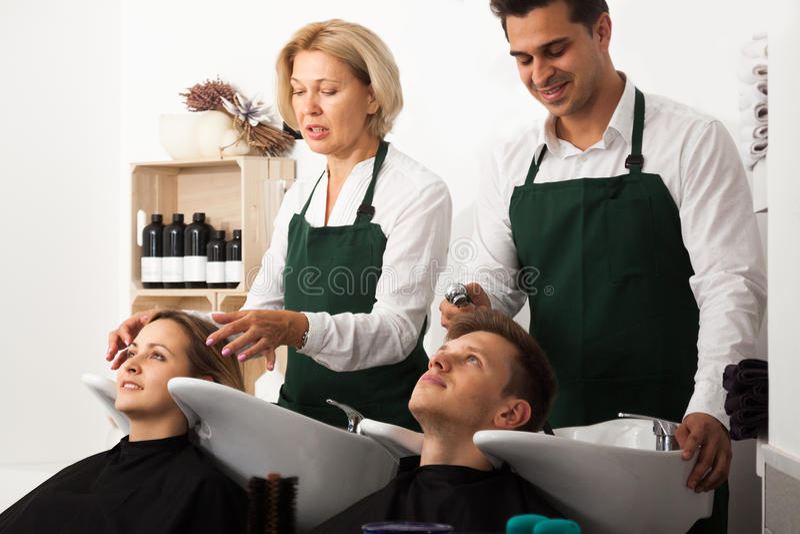 Hairstylistss que lava el pelo de clientes en la peluquería fotos de archivo
