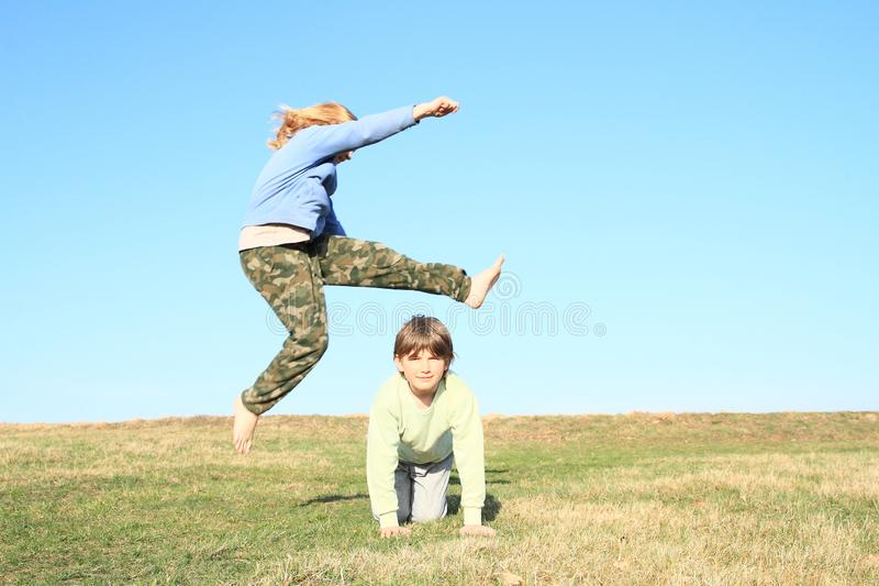 Barefoot girl jumping over boy. Hairy barefoot kid - young barefoot girl with blond hair dressed in khaki pants and blue jacket jumping over young smiling boy stock image