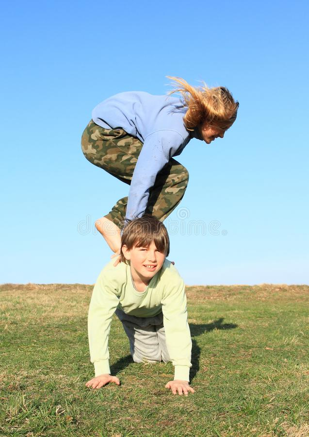 Barefoot girl jumping over boy. Hairy barefoot kid - young smiling girl with blond hair dressed in khaki pants and blue jacket jumping over young smiling boy stock photos