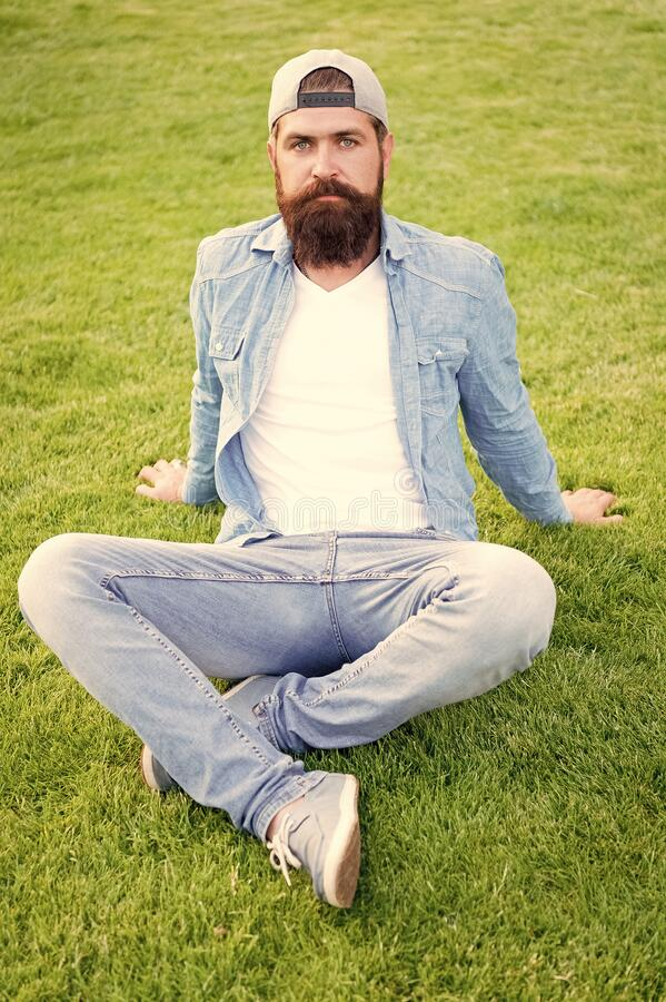 Hairy hipster. Brutal hipster sitting on green grass. Bearded man in trendy hipster style on summer outdoor. Caucasian stock image