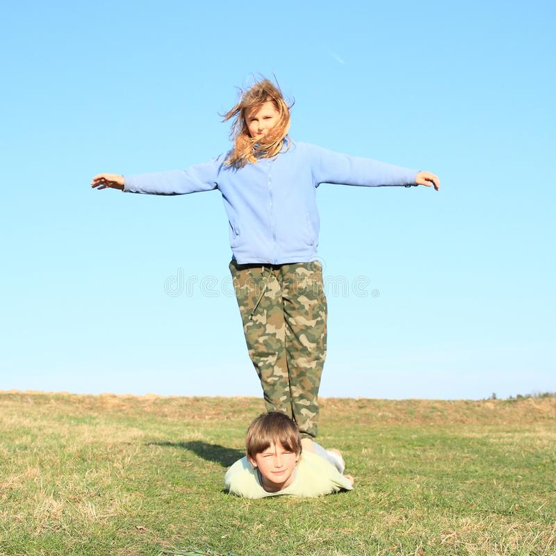 Barefoot girl standing on boy. Hairy kid - young girl with blond hair dressed in khaki pants and blue jacket standing on back of young smiling boy lying on grass royalty free stock photos