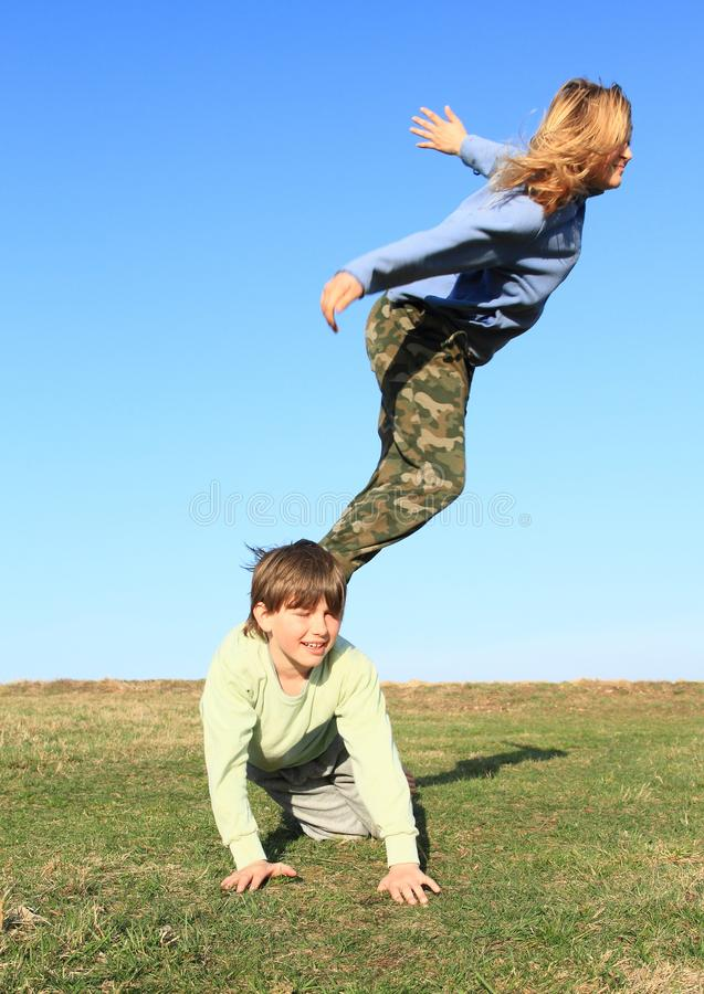 Smiling girl jumping from boy. Hairy kid - young smiling girl with blond hair dressed in khaki pants and blue jacket jumping from young smiling boy kneeling on stock photography