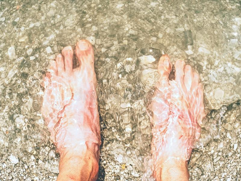 Hairy strong male legs are cooling in cold water of mountain lake royalty free stock image