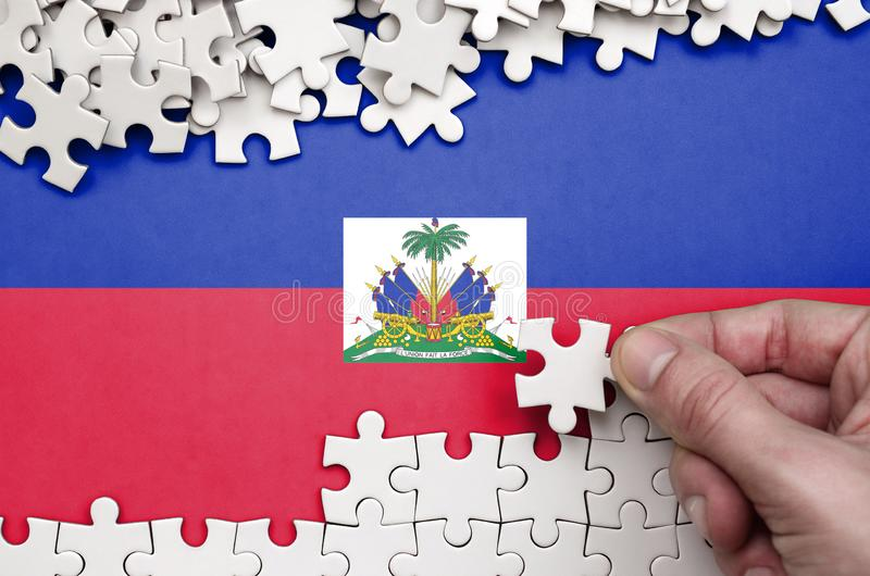 Haiti flag is depicted on a table on which the human hand folds a puzzle of white color stock photos