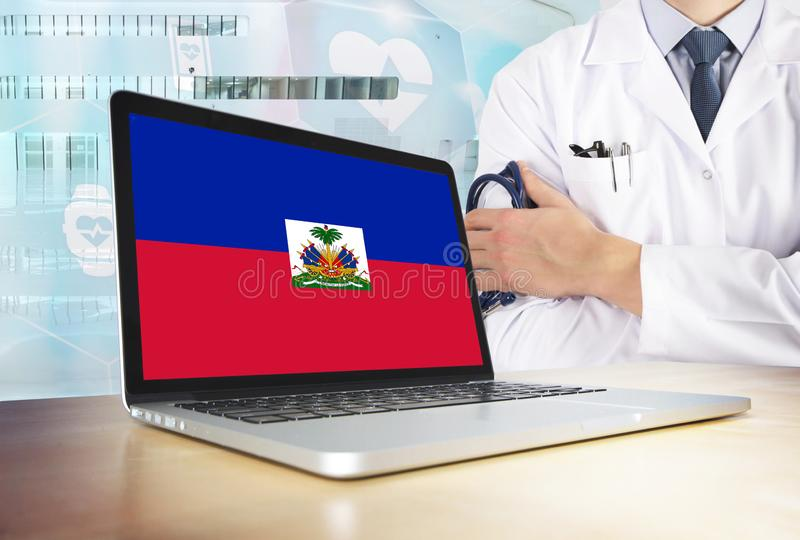 Haiti healthcare system in tech theme. Haitian flag on computer screen. Doctor standing with stethoscope in hospital. Cryptocurrency and Blockchain concept stock photos