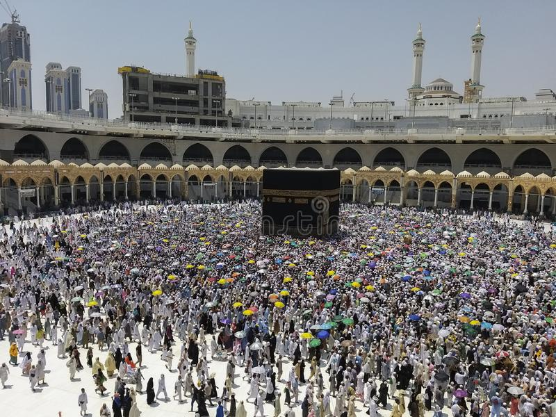 Hajj pilgrims shade themselves from blistering heat with colorful umbrella during hajj season in Makkah, Saudi Arabia.  stock images