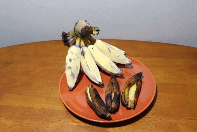 Hak Muk-Banane, thailändische Sprachname Gegrillte und reife Banane im braunen Teller auf dem Holztisch lizenzfreie stockfotos