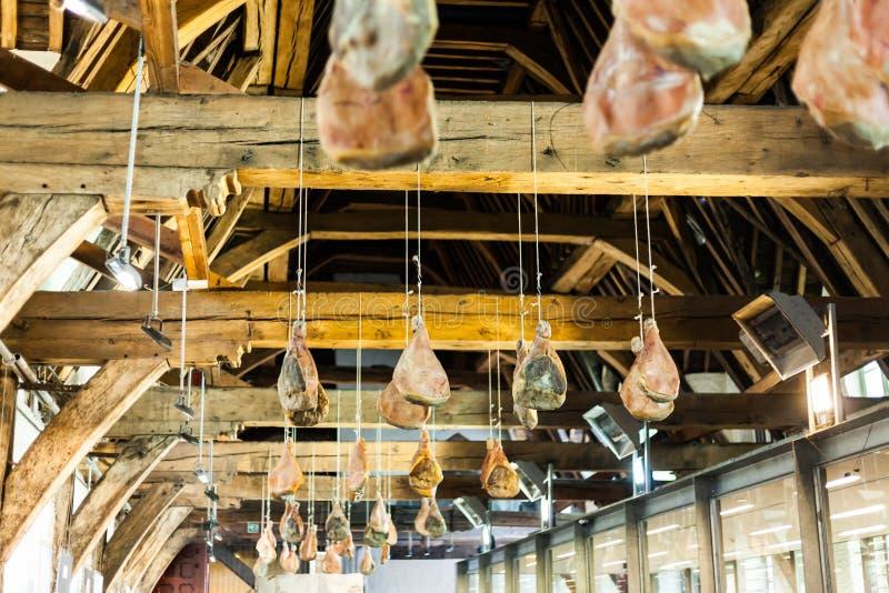 Hakad skinka på trästrålar som hänger från taket Traditionell väg av att torka kött Grisköttskinka som torkar på luften royaltyfri bild